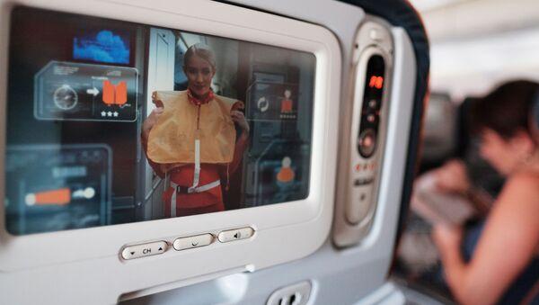 Trên màn hình trước ghế trong khoang máy bay hiển thị cách hành động trong trường hợp xảy ra tai nạn. - Sputnik Việt Nam