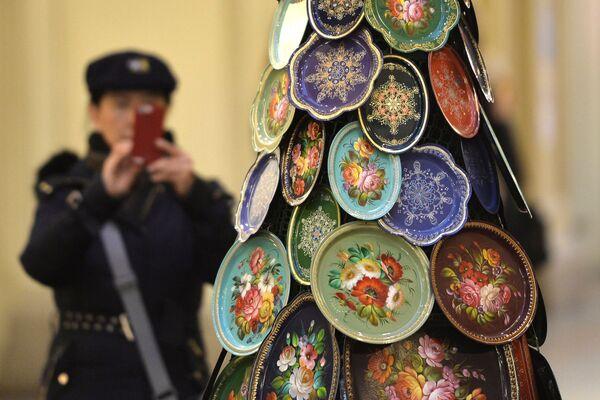 Du khách chụp ảnh cây thông Năm mới được ghép từ các khay truyền thống Zhostovo trong cửa hàng GUM, Moskva. - Sputnik Việt Nam