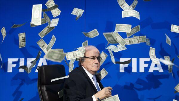 Chủ tịch FIFA Joseph Blatter nhìn những đồng đô la giả mà những người biểu tình ném xuống trong cuộc họp báo tại trụ sở ở Zurich - Sputnik Việt Nam